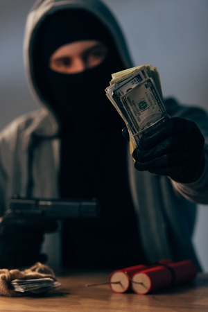 Terrorist in mask and gloves holding gun and dollar banknotes