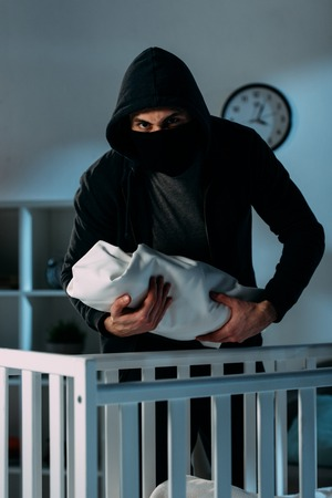 Kidnapper in black clothes and mask holding infant child