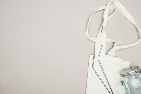 top view of white cotton bag, glass jar and reusable stainless steel straws on grey background Фото со стока