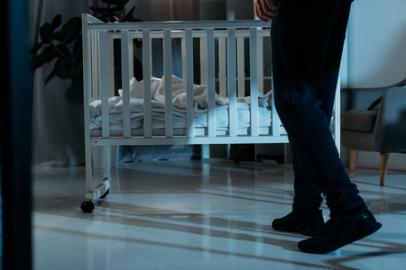 Cropped view of kidnapper in black pants standing near crib in dark room Stock Photo