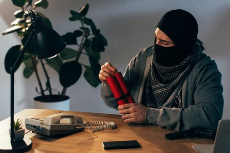 Terrorist in mask sitting at table with dynamite in room Stock Photo