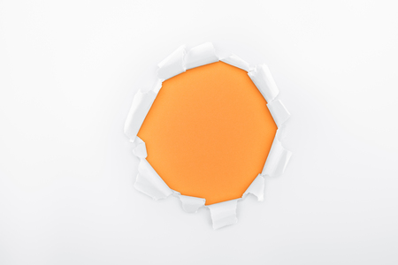 ripped hole in textured white paper on orange background Фото со стока