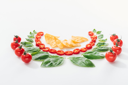 flat lay with nachos, cut chili peppers, basil leaves and ripe cherry tomatoes on white background