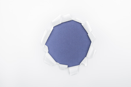 ripped hole in textured white paper on blue dotted background Banque d'images - 120140220