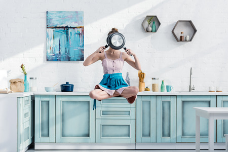 young woman flying in air in lotus pose with pans in front of face Stock Photo