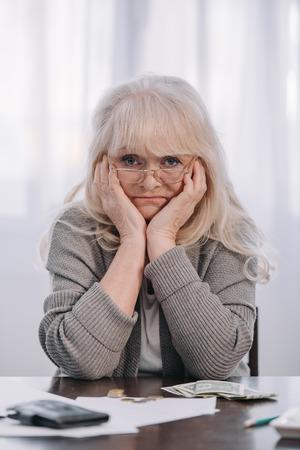 müde ältere Frau, die am Tisch sitzt und den Kopf mit den Händen stützt, während sie zu Hause Geld zählt