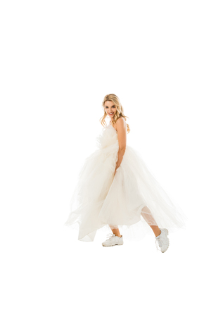 beautiful groom in wedding dress and sneakers dancing while looking at camera isolated on white Stock Photo