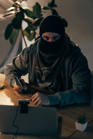 Angry terrorist in mask aiming gun and looking at camera Stock Photo