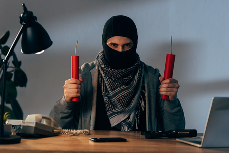 Front view of terrorist with dynamite sitting at table in room