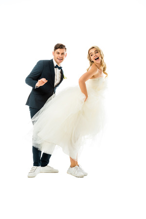 cheerful groom and bride dancing in elegant clothes and sneakers isolated on white