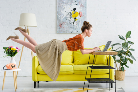 elegant young woman levitating in air and using laptop in living room Stok Fotoğraf