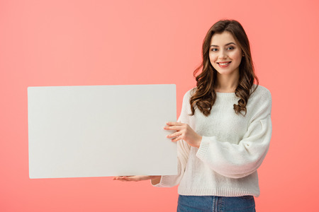 smiling and beautiful woman holding blank placard with copy space isolated on pink