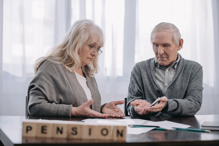 senior couple at table with word 'pension' made of wooden blocks on foreground Imagens
