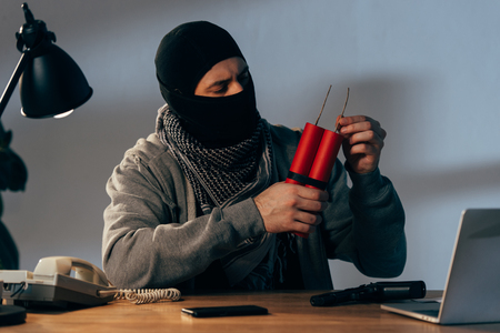 Terrorist in mask holding dynamite while sitting at table in dark room Stock Photo