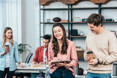 Uśmiechnięty młody człowiek z papierowym kubkiem kawy patrzący na dziewczynę z notatnikiem