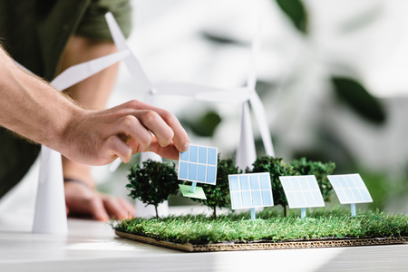 cropped view of man putting solar panels models on grass on table in office Imagens