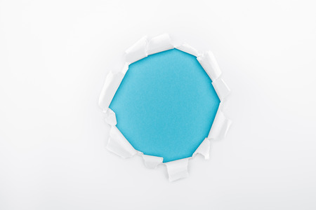tattered hole in white textured paper on blue background