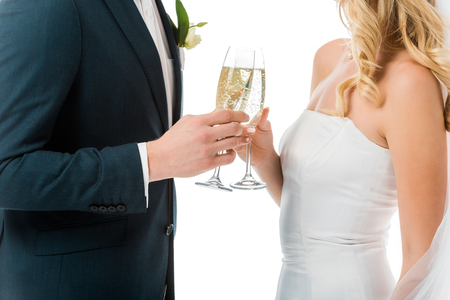 cropped view of bride and groom clinking glasses of champagne isolated on white Imagens