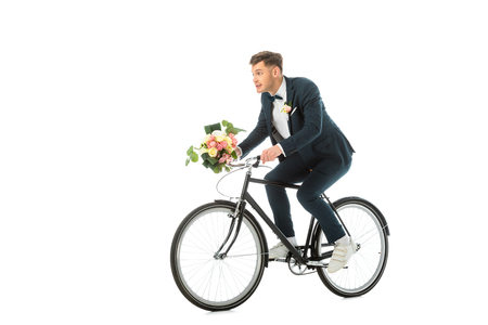 cheerful groom in sneakers riding bike and holding wedding bouquet isolated on white Stock Photo