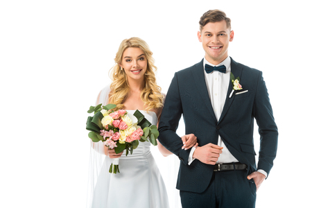 happy bride with wedding bouquet, and smiling groom in black suit isolated on white