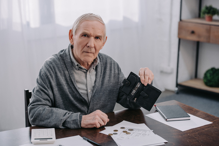 senior man sitting at table with paperwork and holding wallet while counting money at home Stockfoto