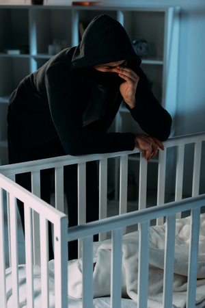 Crying kidnapper in mask and black hoodie standing near crib