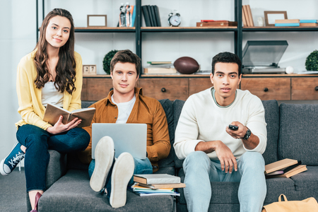 Three multicultural students with notebooks and laptop studying and watching tv Imagens