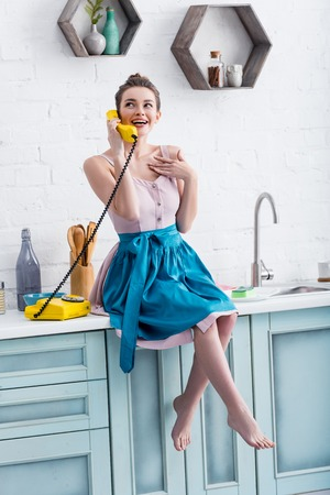 happy young woman in apron sitting on table and talking on vintage yellow telephone in kitchen Stockfoto