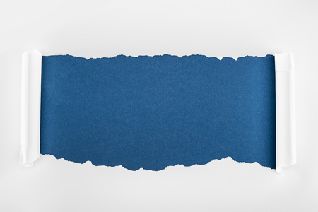 ragged textured white paper with curl edges on deep blue background Banco de Imagens