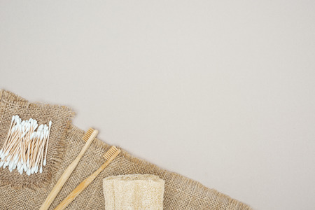 bamboo toothbrushes, organic loofah, cotton swabs and brown sackcloth on grey background