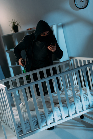 Criminal in mask standing near crib with gun and talking on smartphone