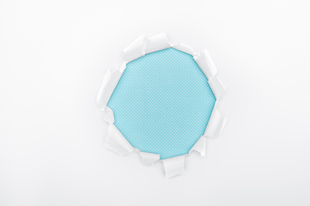 torn hole in textured white paper on light blue background