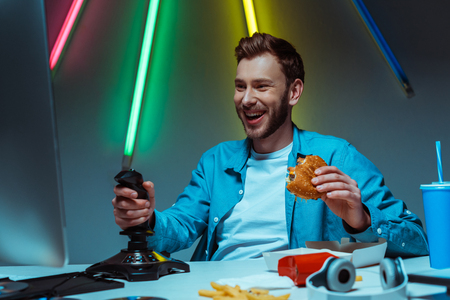 handsome and smiling man holding tasty burger and playing video game with joystick Banque d'images
