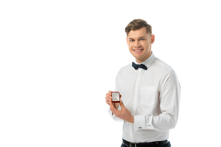 smiling groom holding gift box with wedding ring and looking at camera isolated on white