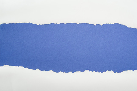 ragged white textured paper with copy space on deep blue background