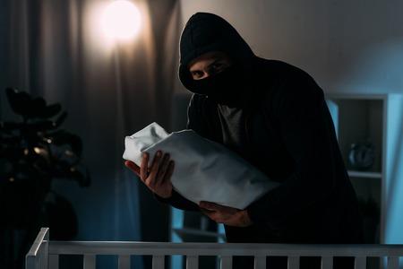Kidnapper in mask and hoodie holding infant child in dark room Zdjęcie Seryjne
