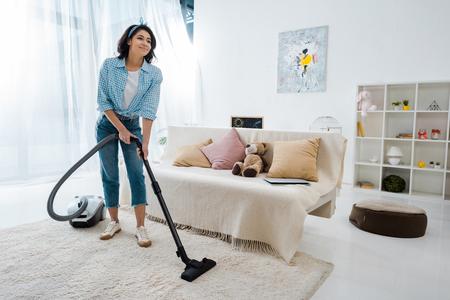 Atractiva mujer afroamericana limpieza de alfombras con aspiradora
