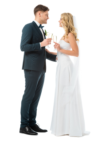 cheerful bride and groom clinking glasses of champagne and looking at each other isolated on white