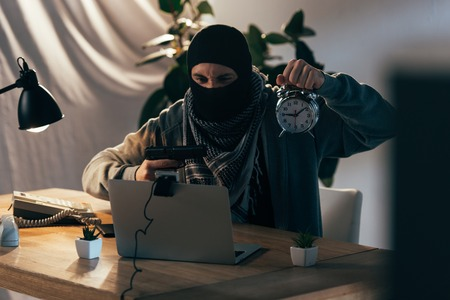 Aggressive terrorist in mask holding gun and showing alarm clock at webcam