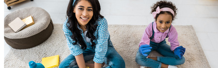 smiling african american mother and daughter sitting on carpet in lotus poses