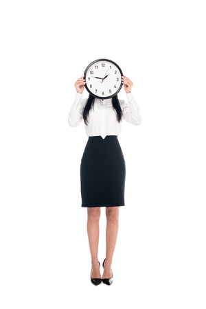 Full length view of brunette businesswoman in shirt holding clock isolated on white