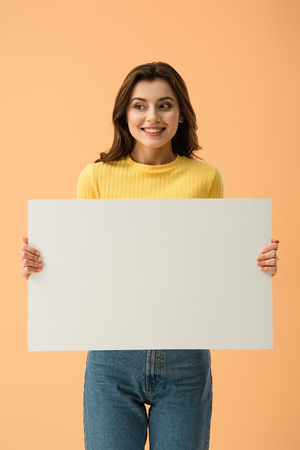 Blissful smiling brunette girl holding blank placard isolated on orange 스톡 콘텐츠