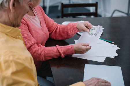 partial view of senior couple holding envelope with roth ira lettering and money while sitting at table Stock Photo