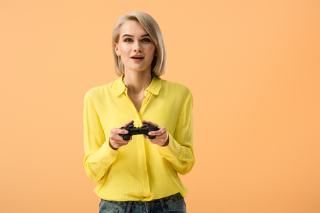 Interested blonde girl in yellow shirt holding gamepad isolated on orange