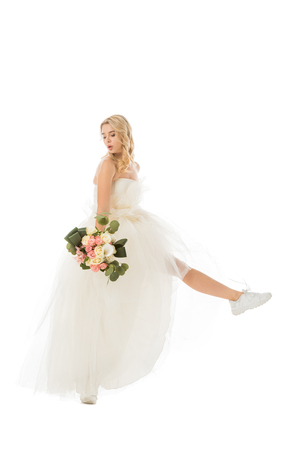 pretty happy bride posing in wedding dress and sneakers isolated on white
