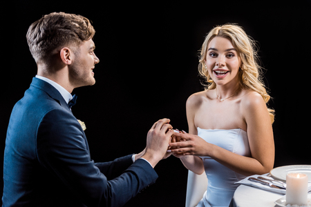 happy young man making marriage proposal to cheerful young woman isolated on black