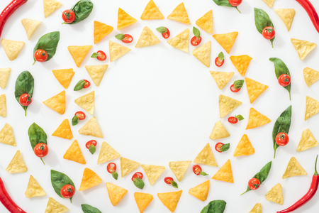 top view of tasty nachos and sliced chili peppers with basil and cherry tomatoes Stock Photo