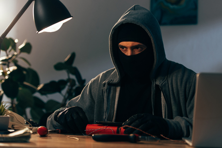 Pensive terrorist in mask and gloves making bomb in room