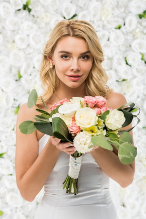beautiful young woman holding wedding bouquet and looking at camera on white floral background