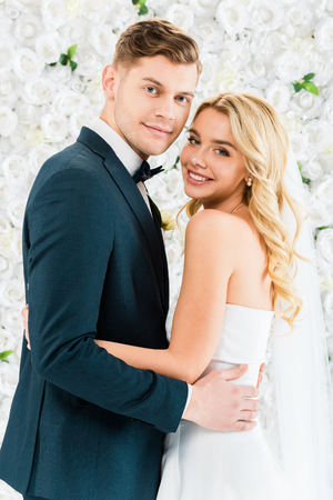 smiling beautiful bride embracing handsome groom on white floral background Stock Photo
